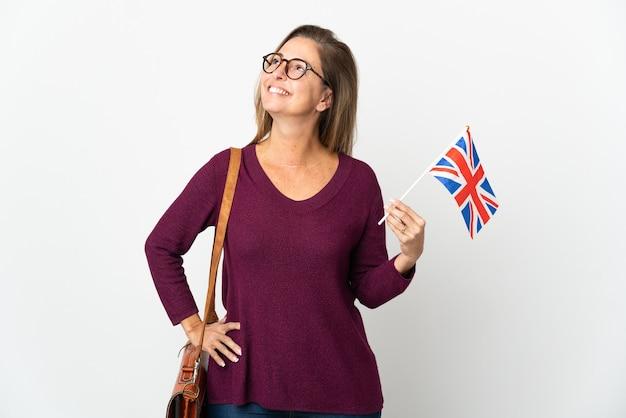 腰に腕と笑顔でポーズをとって白い背景で隔離のイギリス国旗を保持している中年ブラジル人女性