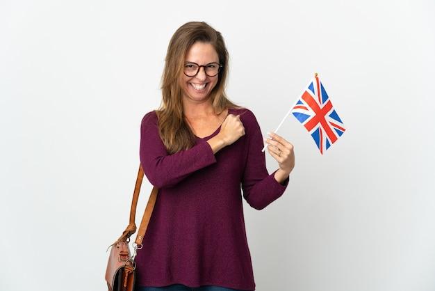 Бразильская женщина среднего возраста, держащая флаг соединенного королевства, изолированная на белой стене, празднует победу