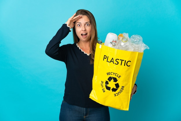 Middle age brazilian woman holding a bag full of plastic bottles