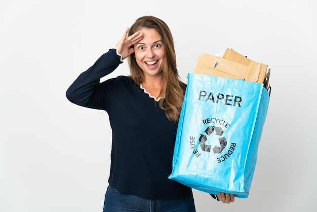 Middle age brazilian woman holding a recycling bag full of paper to recycle over isolated