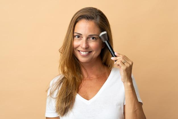 化粧ブラシを保持しているベージュに分離された中年ブラジル人女性