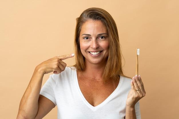 歯ブラシと幸せな表情でベージュに分離された中年ブラジル人女性