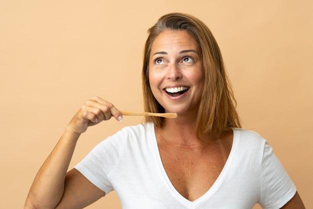 歯ブラシでベージュに分離された中年ブラジル人女性