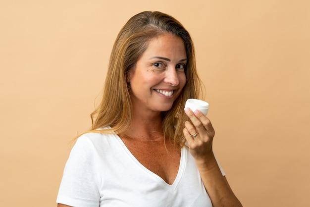 中年のブラジル人女性は、保湿剤とそれを嗅ぐベージュで隔離