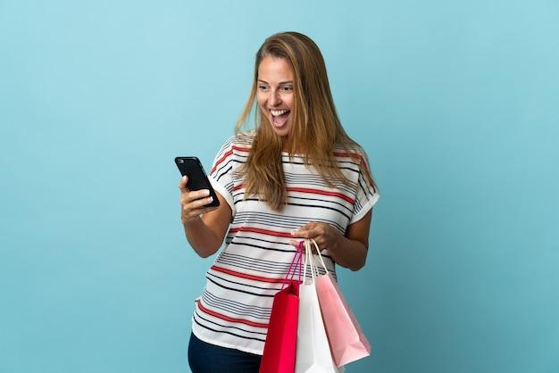 쇼핑 가방을 들고 친구에게 그녀의 휴대 전화로 메시지를 작성하는 파란색 벽에 고립 된 중년 브라질 여자