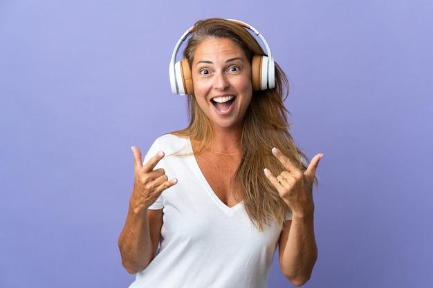 ロックジェスチャーを作る紫色のリスニング音楽に分離された中年ブラジル人女性