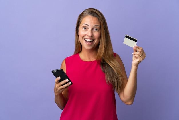 携帯電話で購入し、驚きの表情でクレジットカードを保持している紫色の壁に孤立した中年ブラジル人女性