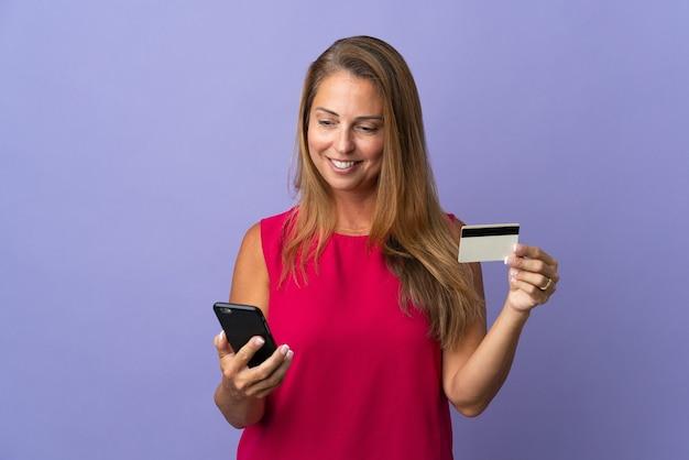 クレジットカードで携帯電話で購入する紫色の壁に分離された中年のブラジル人女性
