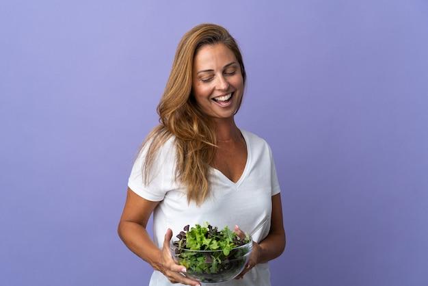 행복 한 표정으로 샐러드 그릇을 들고 보라색 벽에 고립 된 중년 브라질 여자