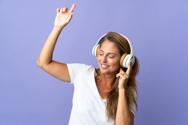 Бразильская женщина среднего возраста изолирована на фиолетовой стене, слушает музыку и танцует