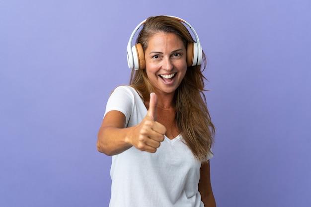 Бразильская женщина среднего возраста изолирована на фиолетовой стене, слушает музыку и с пальцем вверх
