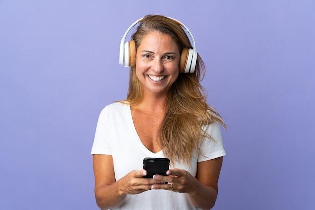 Бразильская женщина среднего возраста изолирована на фиолетовой стене, слушает музыку с помощью мобильного телефона и смотрит вперед