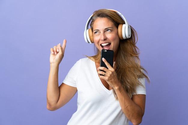 Бразильская женщина среднего возраста изолирована на фиолетовой стене, слушает музыку с помощью мобильного телефона и поет