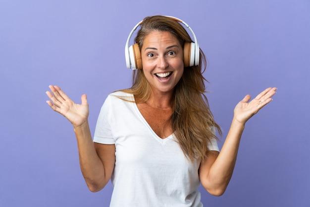 Бразильская женщина среднего возраста, изолированная на фиолетовой стене, удивлена и слушает музыку