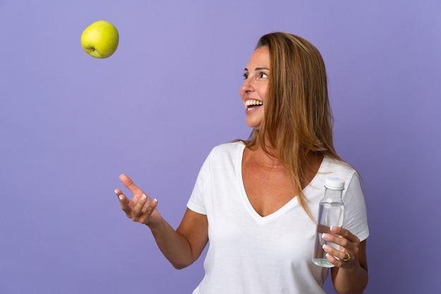 Бразильская женщина среднего возраста изолирована на фиолетовой стене с яблоком и с бутылкой воды
