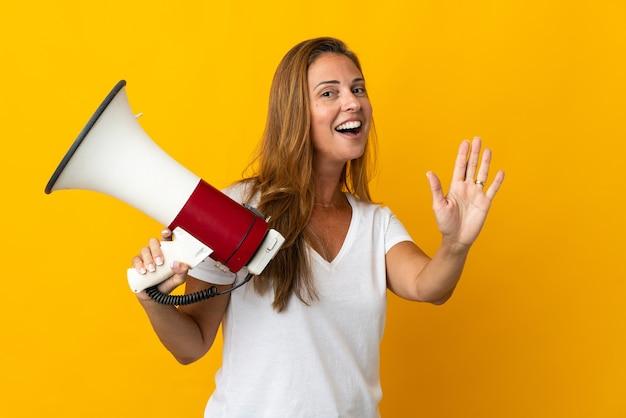 Бразильская женщина среднего возраста изолирована на желтом, держит мегафон и салютует рукой со счастливым выражением лица