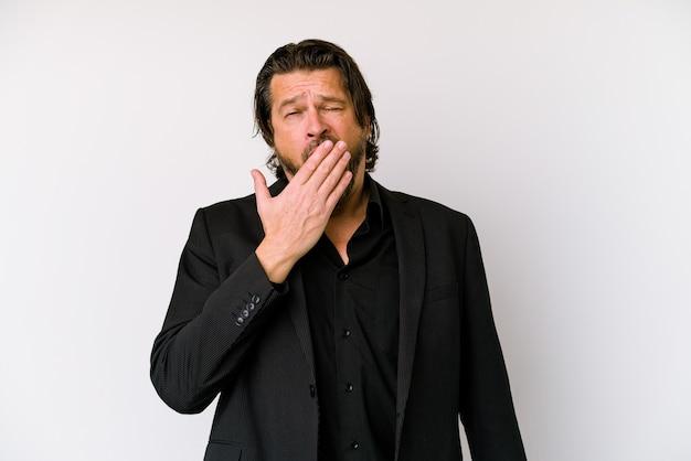 手で口を覆う疲れたジェスチャーを示すあくびをしている白い背景に分離された中年のビジネスオランダ人。