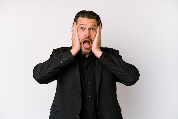 Middle age business dutch man isolated on white background being shocked due to an imminent danger