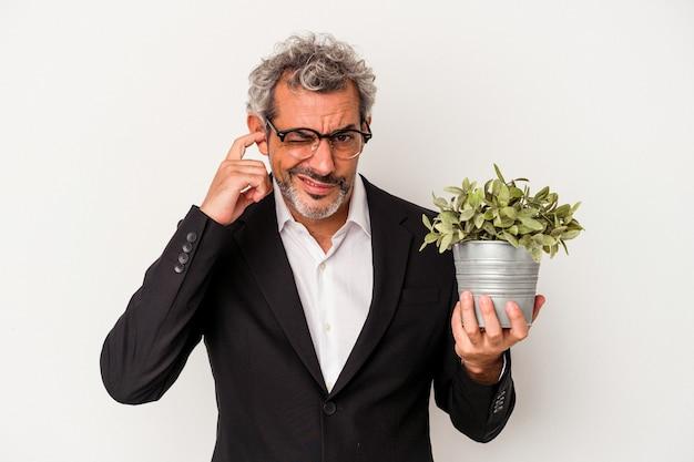 手で耳を覆う白い背景で隔離の植物を保持している中年のビジネスマン。