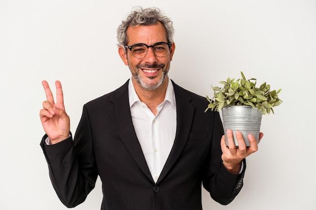 指で平和のシンボルを示す、楽しくてのんきな白い背景で隔離の植物を保持している中年のビジネスマン。