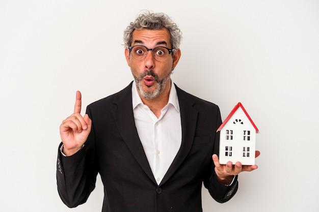 いくつかの素晴らしいアイデア、創造性の概念を持っている青い背景に分離された手形と家のモデルを保持している中年のビジネスマン。
