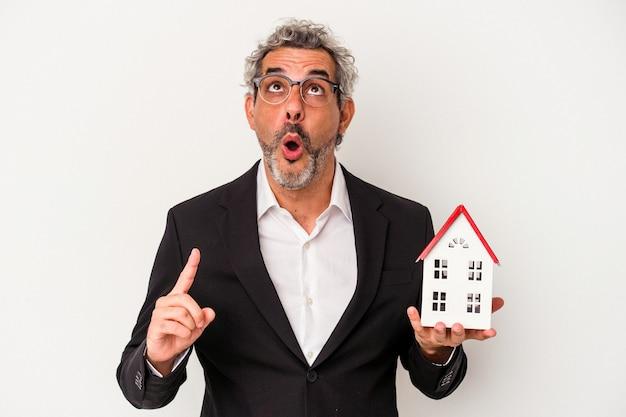 파란 배경에 격리된 지폐와 집 모델을 들고 있는 중년 사업가가 입을 벌리고 거꾸로 가리키고 있습니다.