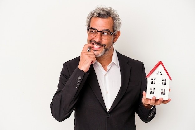 파란색 배경에 격리된 지폐와 주택 모델을 들고 있는 중년 사업가는 복사 공간을 바라보는 무언가에 대해 편안하게 생각했습니다.
