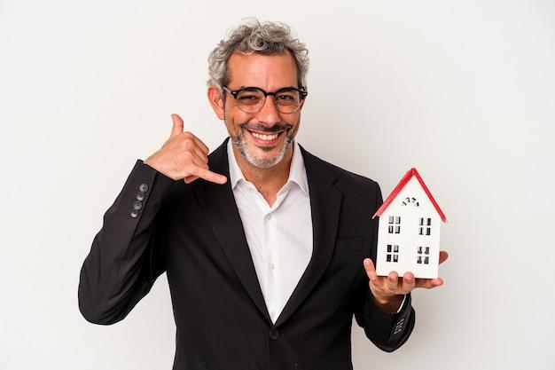 手形を保持している中年のビジネスマンと指で携帯電話の呼び出しジェスチャーを示す青い背景に分離された家のモデル。
