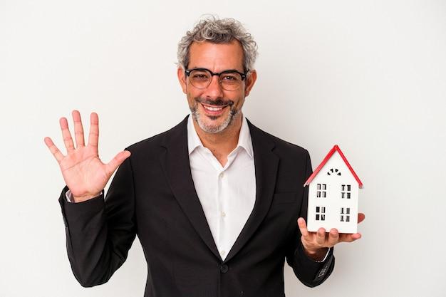 手形を保持している中年のビジネスマンと青い背景に分離された家のモデルは、指で5番を示して陽気に笑っています。