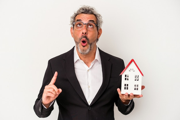 Middle age business man holding bills and house model isolated on blue background  pointing upside with opened mouth.