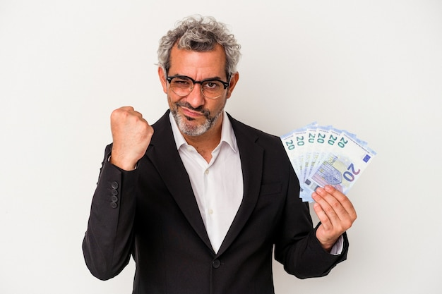 Middle age business man holding bills isolated on blue background  showing fist to camera, aggressive facial expression.