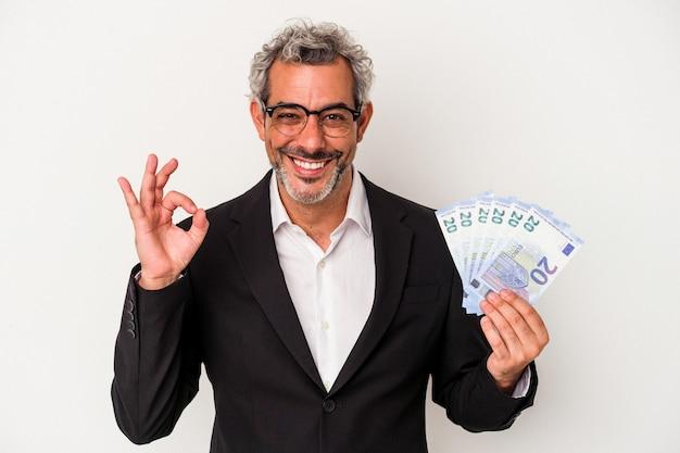 파란색 배경에 격리된 지폐를 들고 있는 중년 사업가는 쾌활하고 자신감 있는 제스처를 보여줍니다.