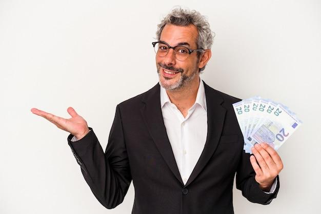 手のひらにコピースペースを示し、腰に別の手を保持している青い背景で隔離の請求書を保持している中年のビジネスマン。