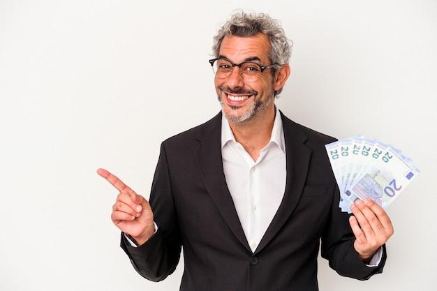 파란색 배경에 격리된 지폐를 들고 있는 중년 사업가는 웃고 옆으로 가리키며 빈 공간에 뭔가를 보여주고 있습니다.