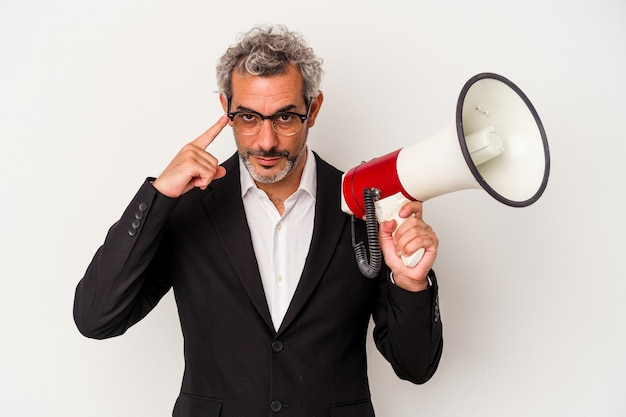 Middle age business man holding a megaphone isolated on white background  pointing temple with finger, thinking, focused on a task.