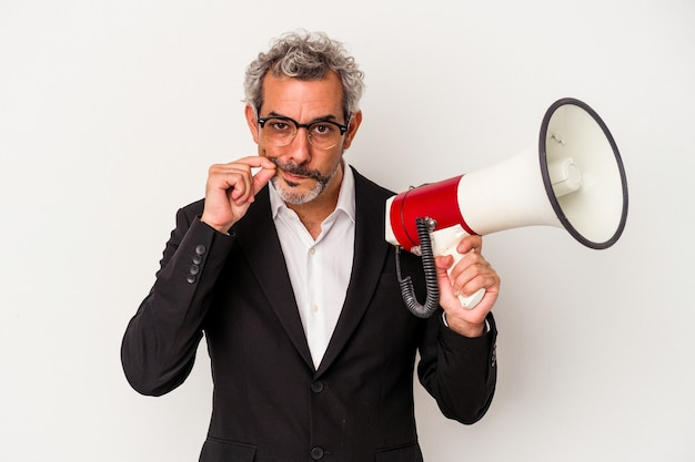 Middle age business man holding a megaphone isolated on white background  with fingers on lips keeping a secret.