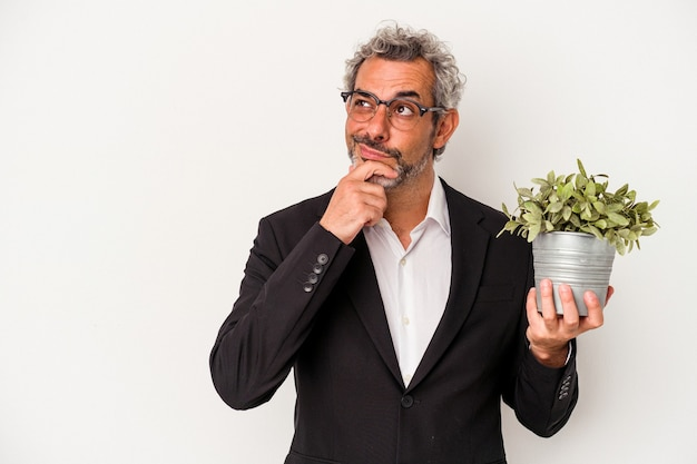 Middle age business man holding a plant isolated on white background  looking sideways with doubtful and skeptical expression.