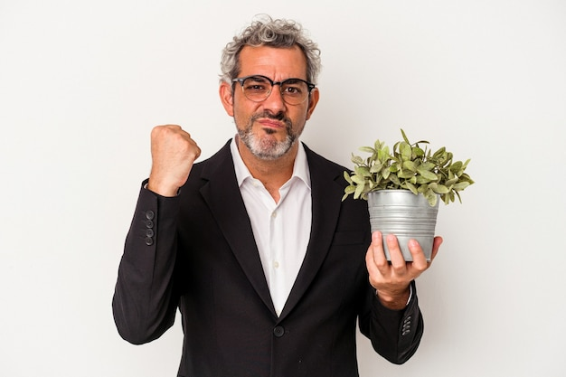 Middle age business man holding a plant isolated on white background  showing fist to camera, aggressive facial expression.