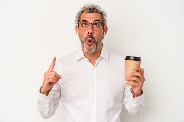 Middle age business man holding a take away coffee isolated on white background  pointing upside with opened mouth.