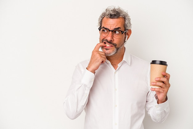 Middle age business man holding a take away coffee isolated on white background  relaxed thinking about something looking at a copy space.