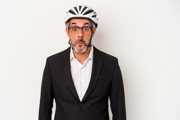青い背景に分離された自転車のヘルメットを身に着けている中年のビジネスマンは、肩をすくめ、目を開けて混乱します。