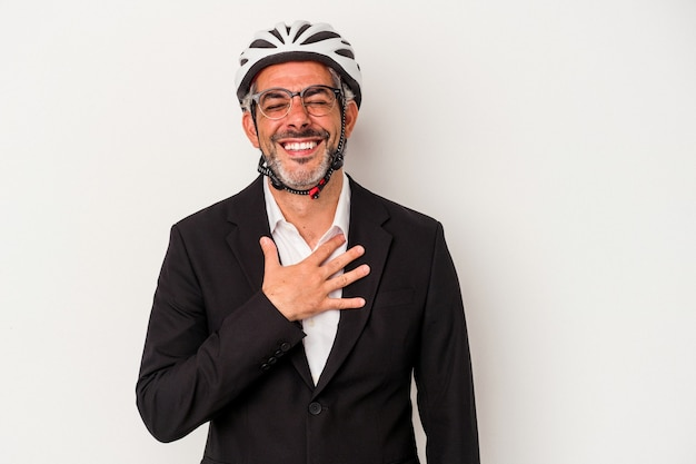 Middle age business man wearing a bike helmet isolated on blue background  laughs out loudly keeping hand on chest.