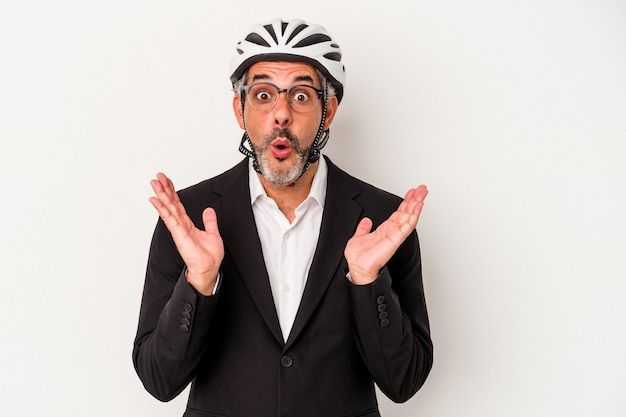 Middle age business man wearing a bike helmet isolated on blue background  surprised and shocked.