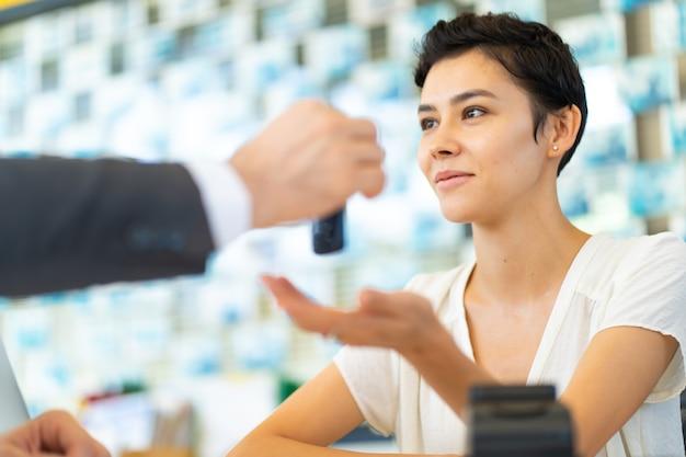 あごひげを生やした中年のビジネスマンは、車のメンテナンスステーションと自動車サービスガレージで顧客サービスに車の鍵を与えます