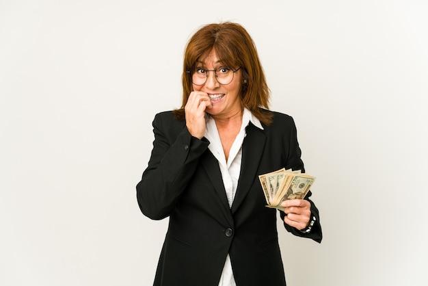 Деловая женщина среднего возраста держит изолированные банкноты, кусая ногти, нервная и очень взволнованная
