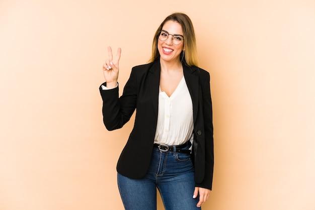 勝利の兆候を示し、広く笑顔を示すベージュの背景に分離された中年のビジネス女性。