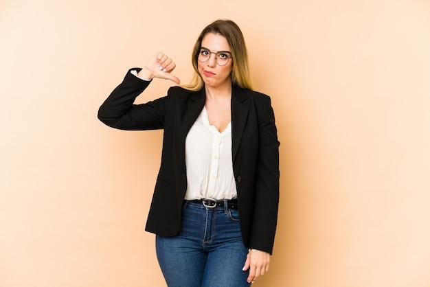 중간 나이 비즈니스 여자 싫어하는 제스처를 보여주는 베이지 색에 아래로 엄지 손가락. 동의하지 않는 개념.