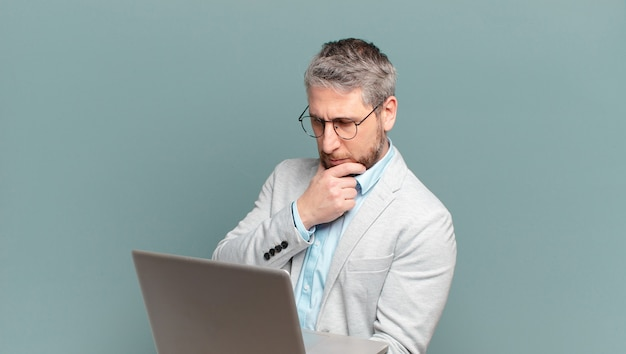 ノートパソコンを持つ中年のビジネスマン