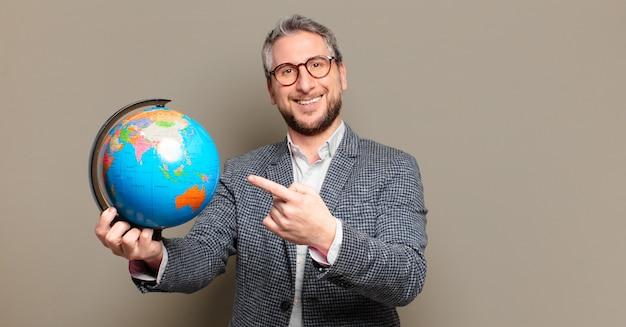 世界の地球地図を持つ中年の実業家