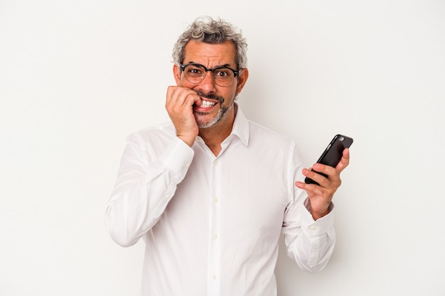 Middle age caucasian business man holding a mobile phone isolated on white background  biting fingernails, nervous and very anxious.